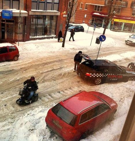 Permobil bogserar bil i snöstormen